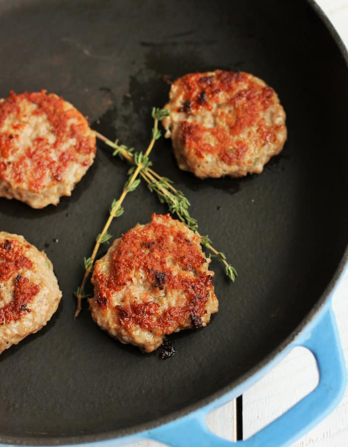 homemade breakfast sausage patties in a cast iron skillet with sprigs of fresh thyme