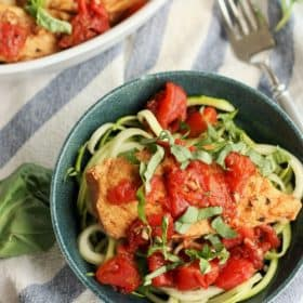 bruschetta chicken on zucchini noodles in a blue bowl topped with basil