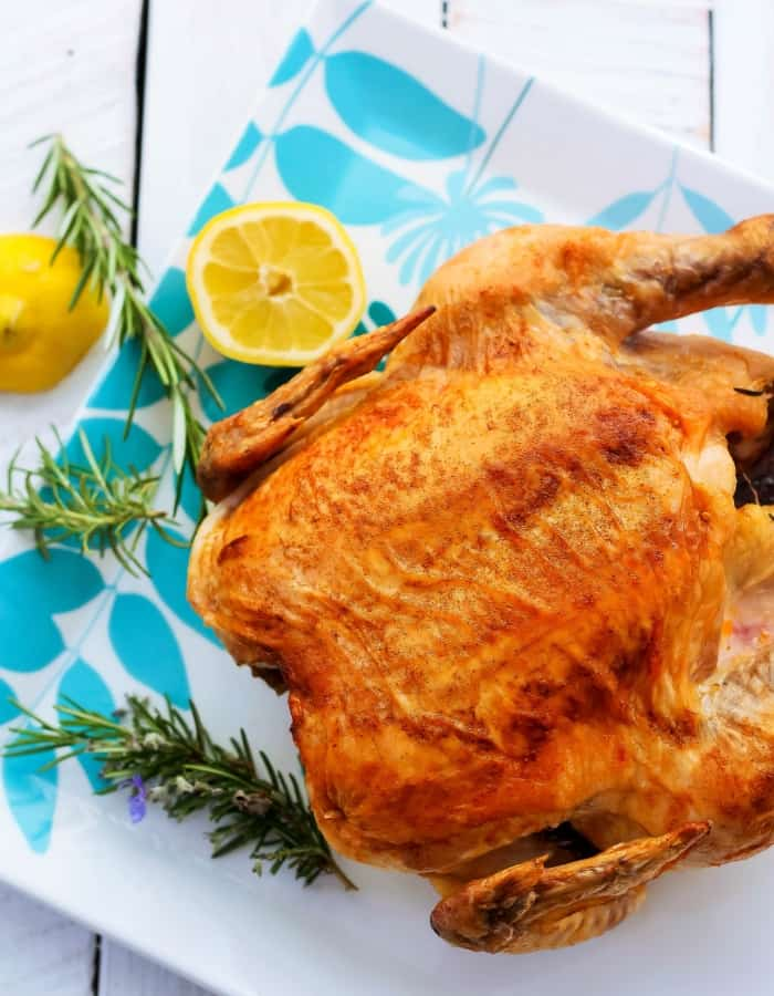 a crispy paleo roasted chicken with lemon and herbs on a plate