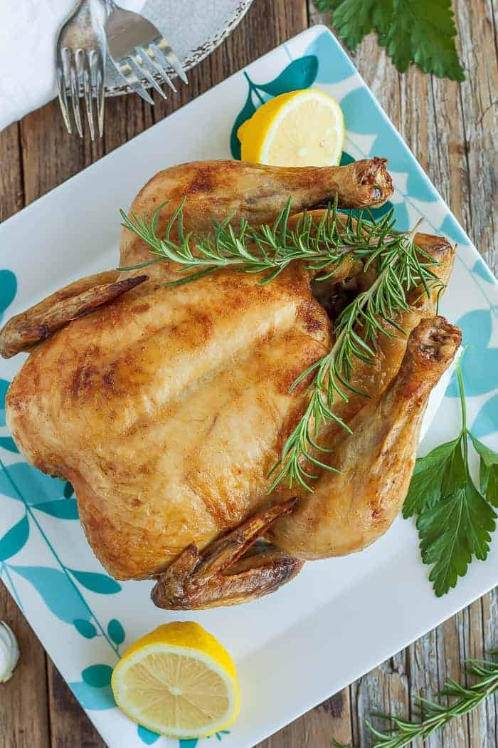 paleo roast chicken on a white plate with herbs and lemon