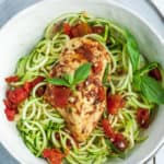 a white bowl with zoodles and bruschetta chicken topped with basil and tomatoes