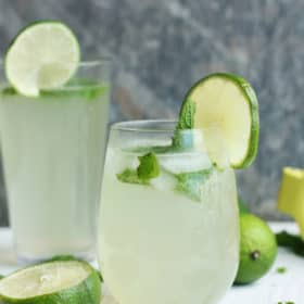 Two glasses of virgin mojitos with lime and mint on a white board
