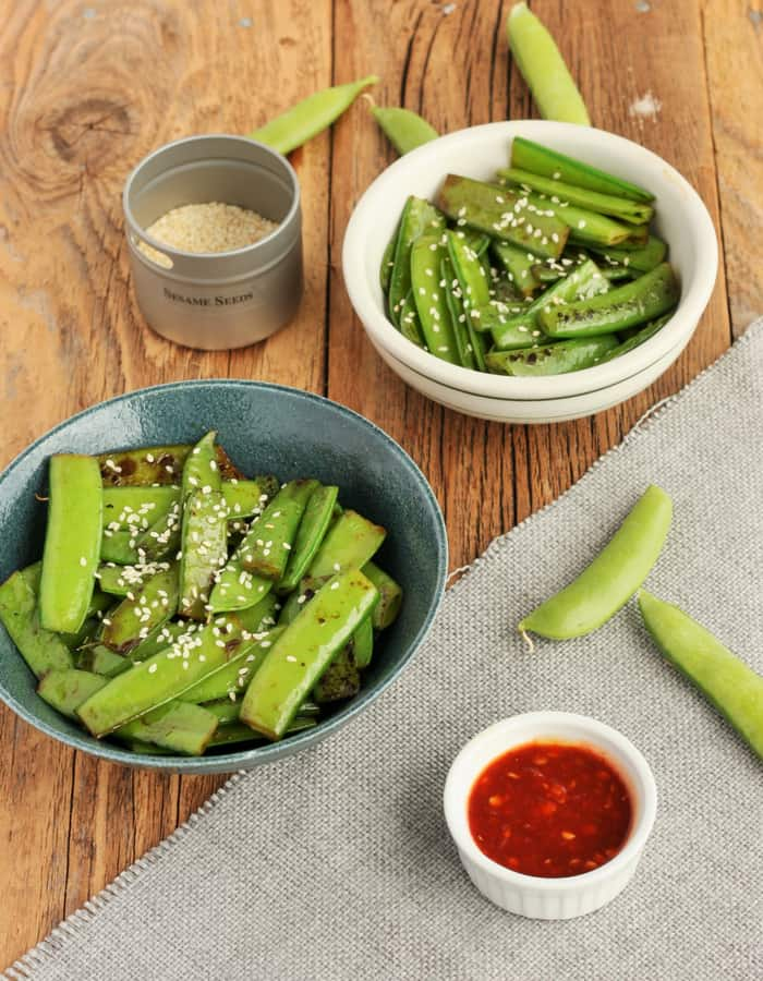 two bowls of sesame snow peas and sesame seeds on a wooden board