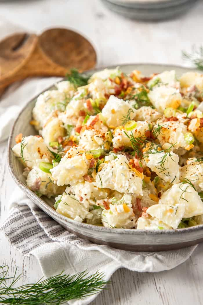 a bowl of potato salad topped with dill, bacon, and cheese