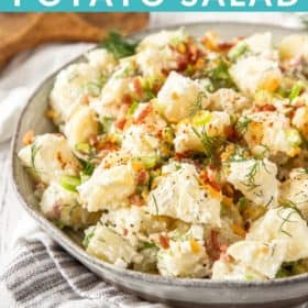 A bowl of instant pot potato salad topped with dill, bacon, and green onions