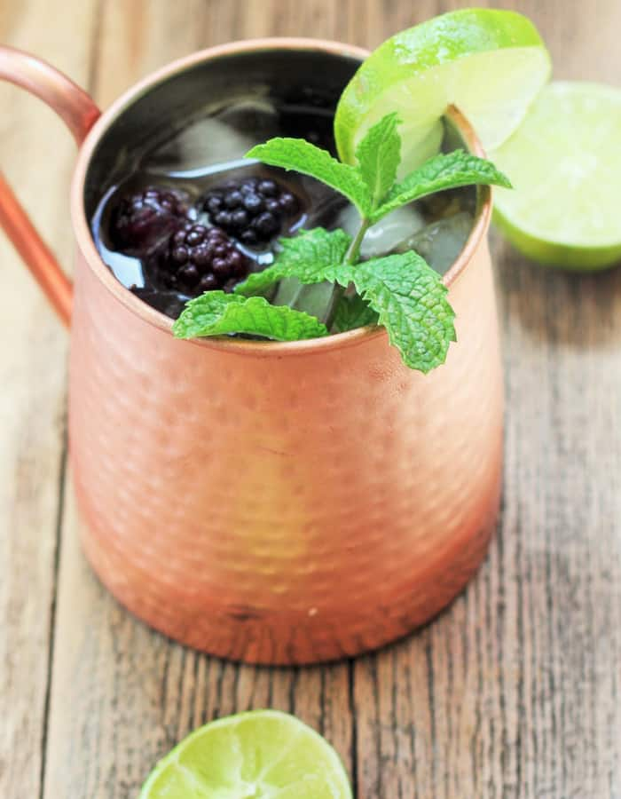 a blackberry and peach moscow mule in a copper cup with mint and blackberries