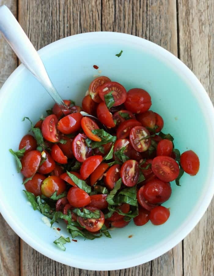 Tomatoes with garlic and basil in a bowl with a spoon