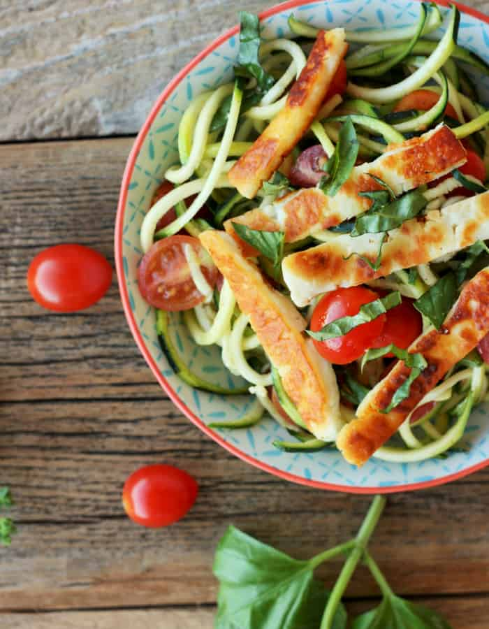 fried halloumi with tomatoes and zoodles in a bowl