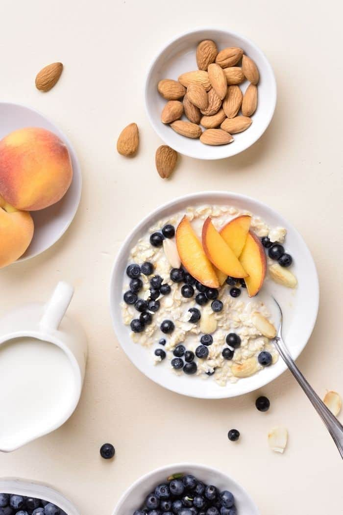 a bowl of oatmeal topped with sliced peaches and blueberries