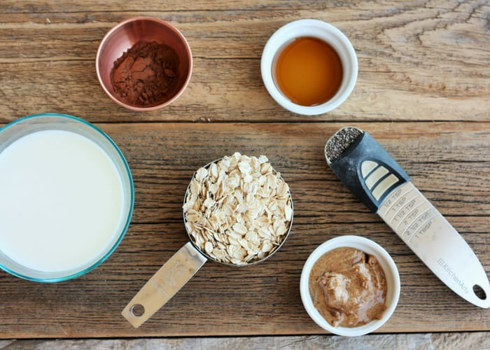 a wooden board with oats, milk, and other ingredients for peanut butter overnight oats
