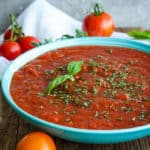 a bowl of crockpot spaghetti sauce with tomatoes and herbs