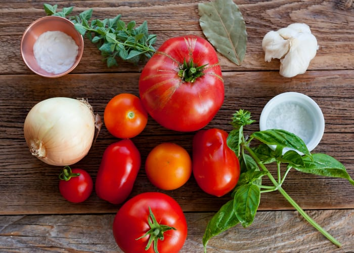 tomatoes, garlic, and herbs on a wooden board