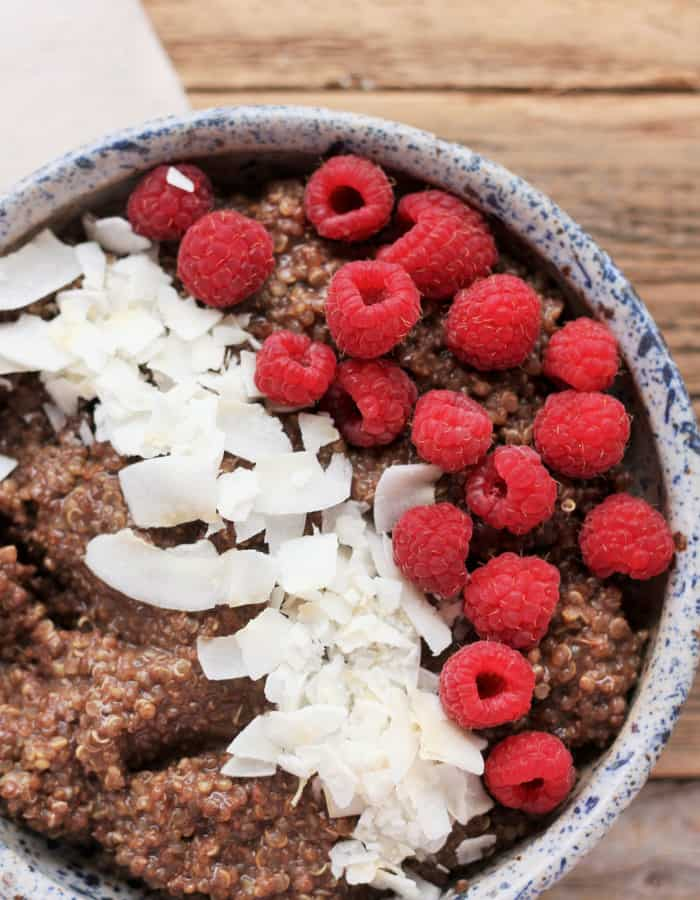 chocolate quinoa in a bowl with raspberries and coconut flakes