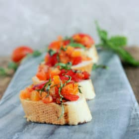 four pieces of tomato bruschetta on a grey cheese board