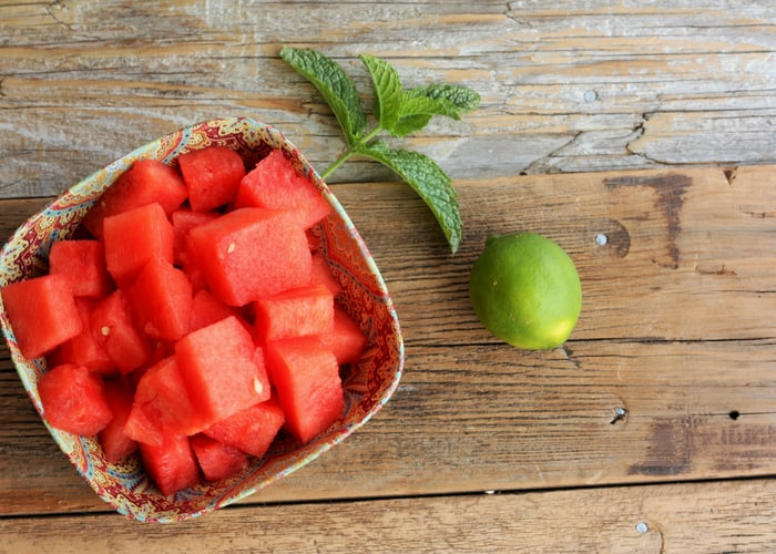 cubed watermelon in a bowl with mint and a lime on a wooden board