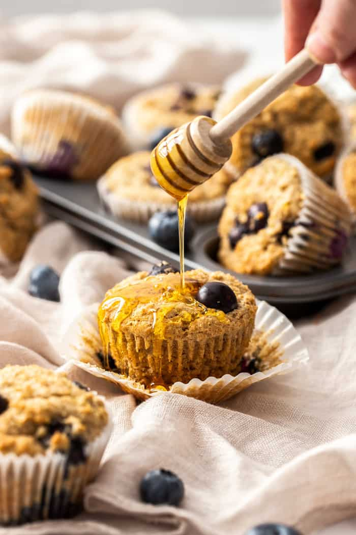honey being drizzled over a whole wheat blueberry muffin