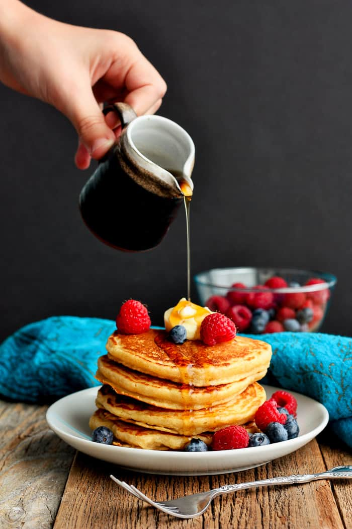 A stack of whole wheat pancakes topped with berries and butter and syrup being poured over it