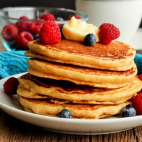 A stack of whole grain pancakes topped with berries