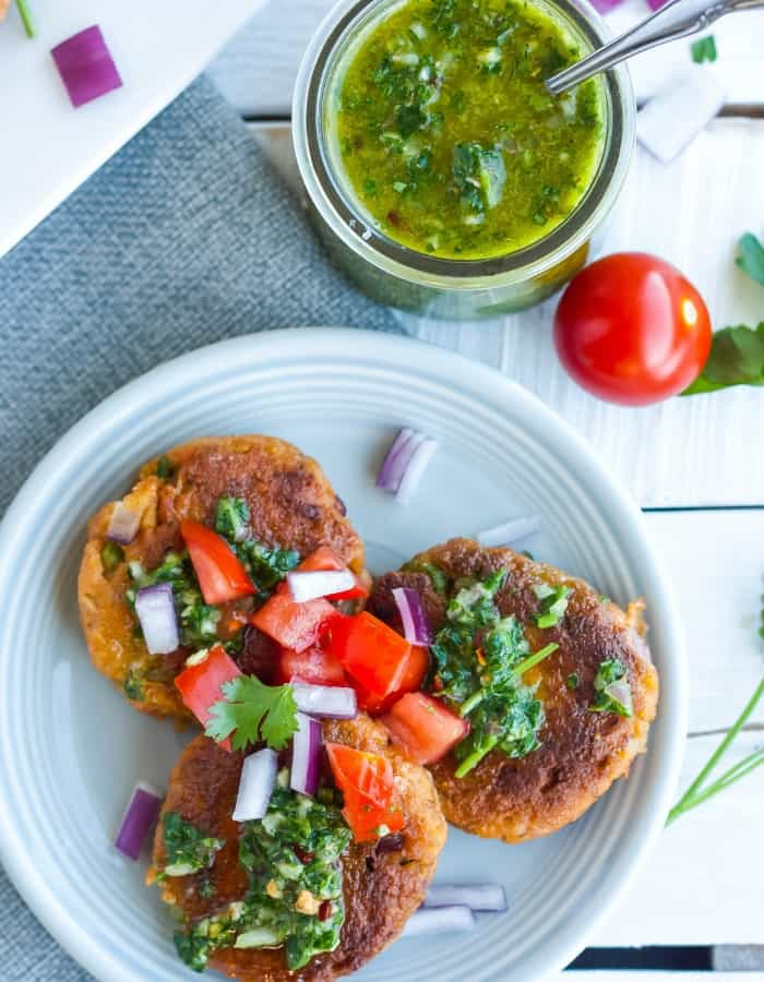 paleo salmon cakes on a plate with chimichurri and tomatoes