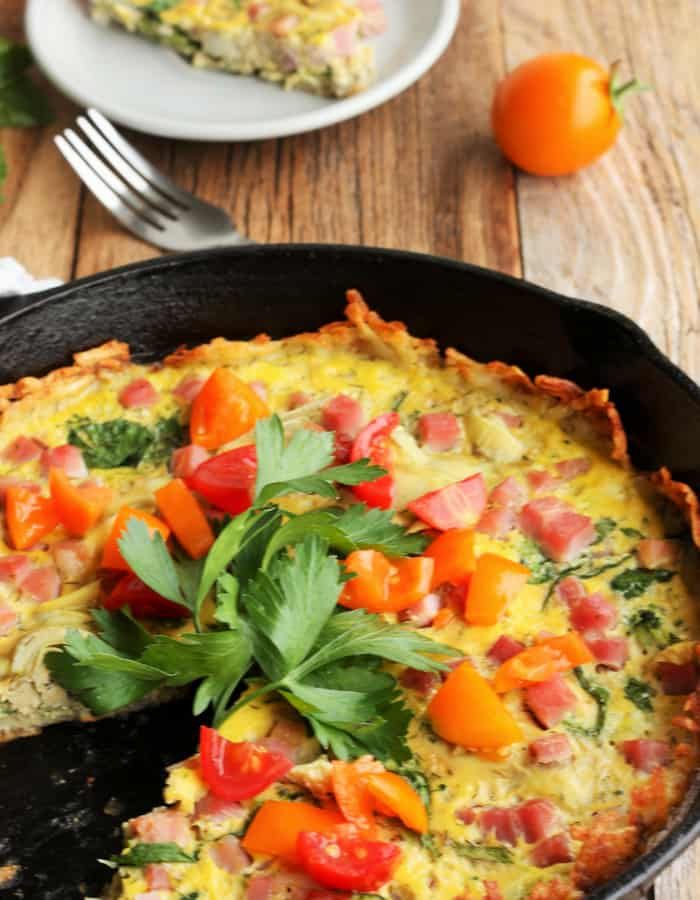 A quiche with hash brown crust in a cast iron pan