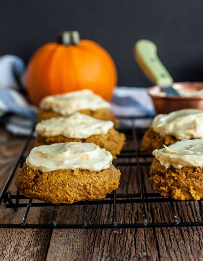whole wheat soft pumpkin cookies with frosting on a cooling rack with pumpkins in the background
