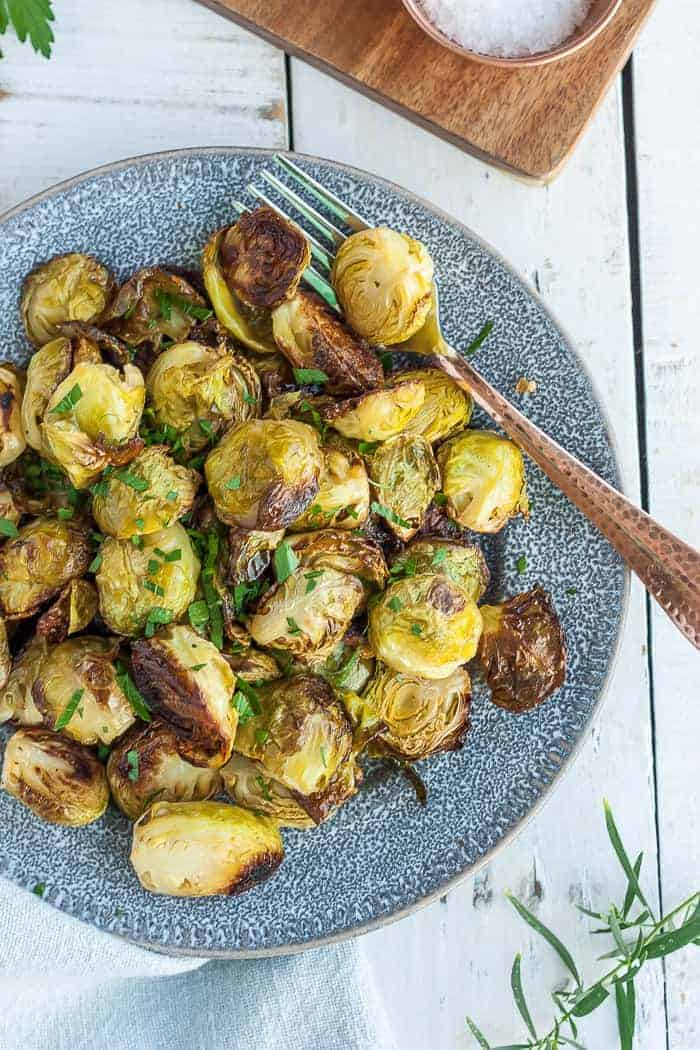 crispy brussels sprouts on a grey plate with a fork