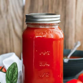 a quart jar of tomato soup with basil on a wooden board