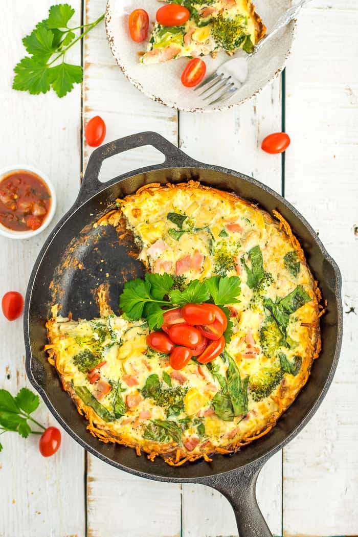 gluten-free quiche in a cast iron skillet topped with parsley and sliced tomatoes