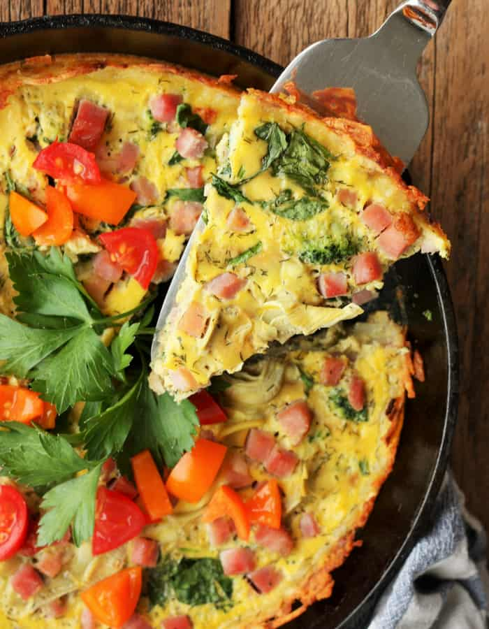 A slice of whole30 quiche in a cast iron pan with a serving spoon