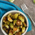 A bowl of roasted brussels sprouts with garlic, a fork, and blue cloth