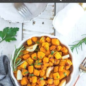 a white scalloped bowl with cubes of crispy butternut squash with afork on a white board
