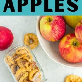 a jar of dried apples tipped on its side with a bowl of apples on a white board