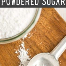 a spoon and glass of powdered sugar on a wooden cutting board