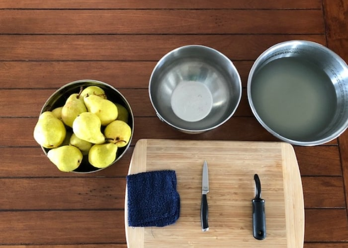 A cutting board with bowls, knife, pears, and a vegetable peeler