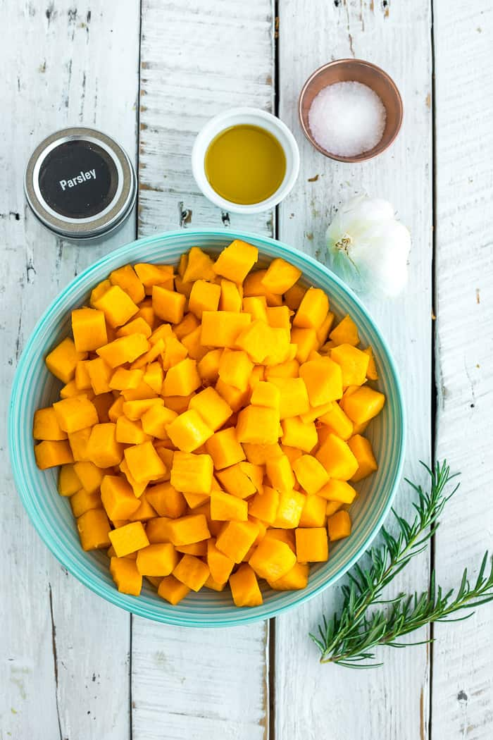 a blue bowl with cubes of butternut squash, olive oil, salt, and garlic