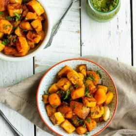 Two bowls of oven-roasted butternut squash with chimichurri sauce on a white board