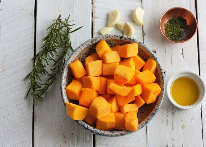 a bowl of roast butternut squash cubes, rosemary, and garlic on a white board