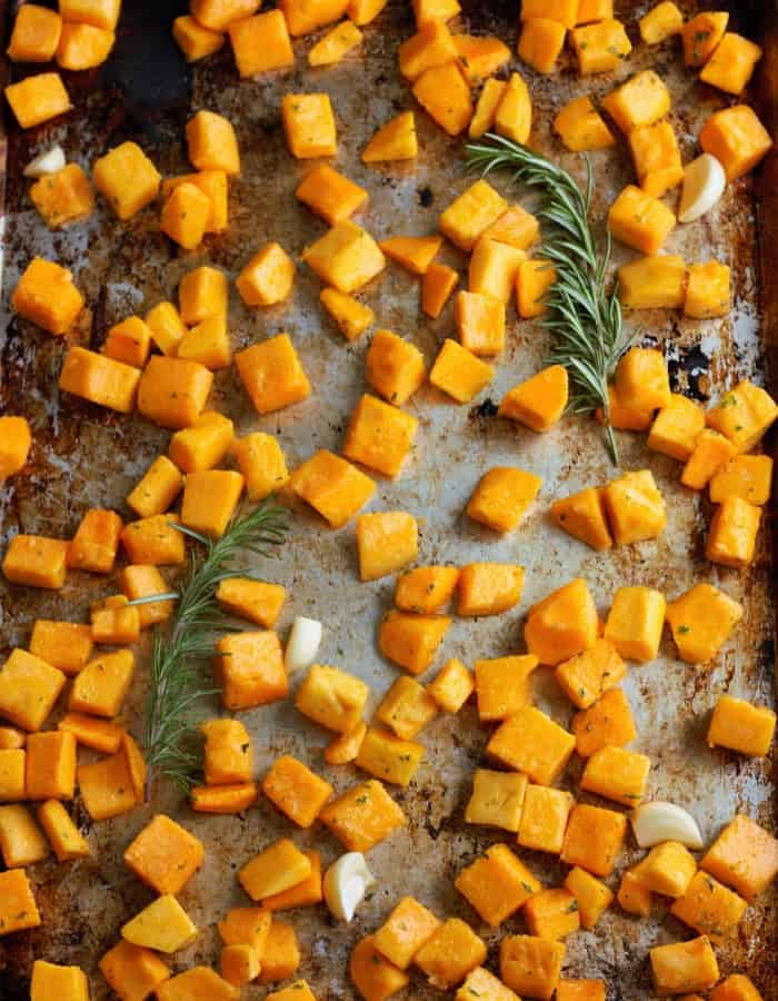 roast butternut squash cubes on a baking pan with rosemary
