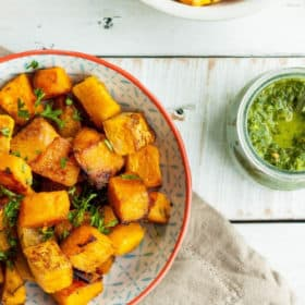 a bowl of oven-roasted butternut squash with a dish of chimichurri