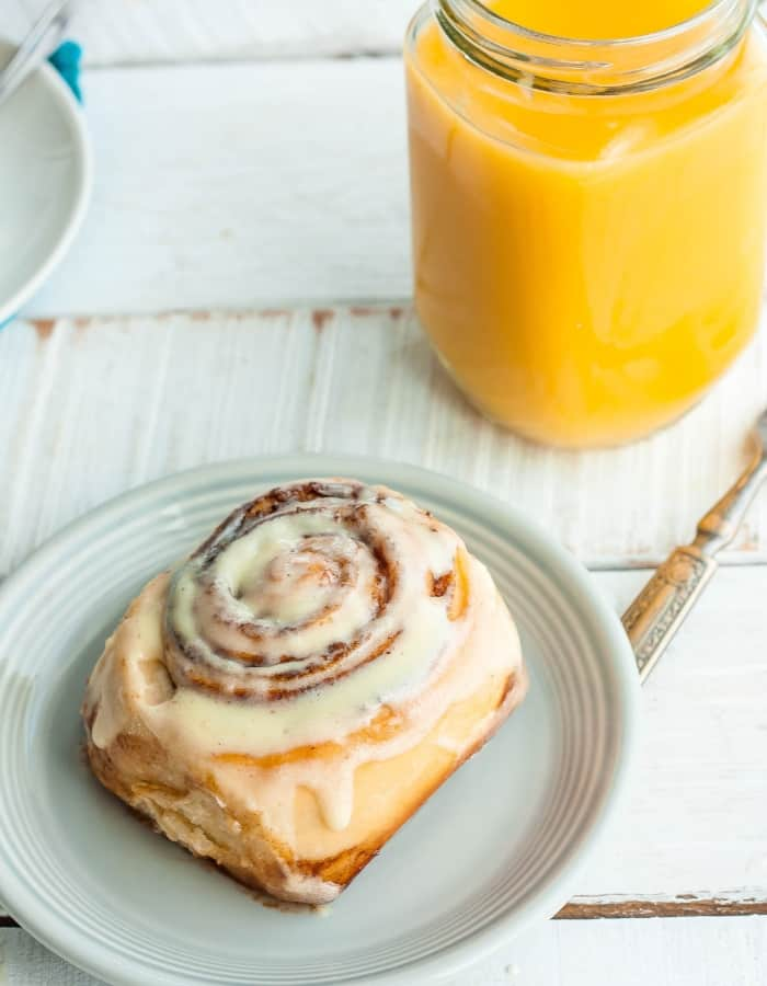 a plate with an overnight cinnamon roll, a fork and orange juice