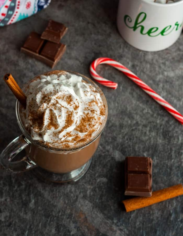 a mug of slow cooker hot chocolate with a candy cane for make ahead christmas morning breakfasts