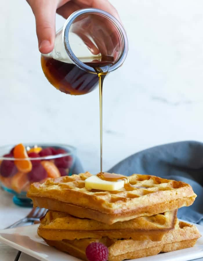 syrup being poured over eggnog waffles for make ahead christmas morning breakfasts