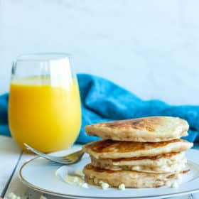a stack of cinnamon pancakes with a glass of orange juice