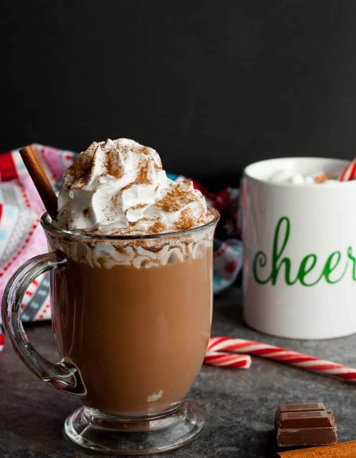 Two mugs of slow cooker hot chocolate with candy canes and cinnamon sticks