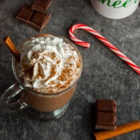 two mugs of slow cooker hot chocolate with a candy cane and cinnamon stick