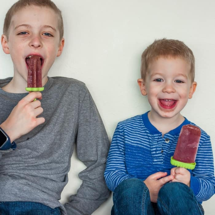 Two kids holding healthy tea popsicles for sore throats and smiling