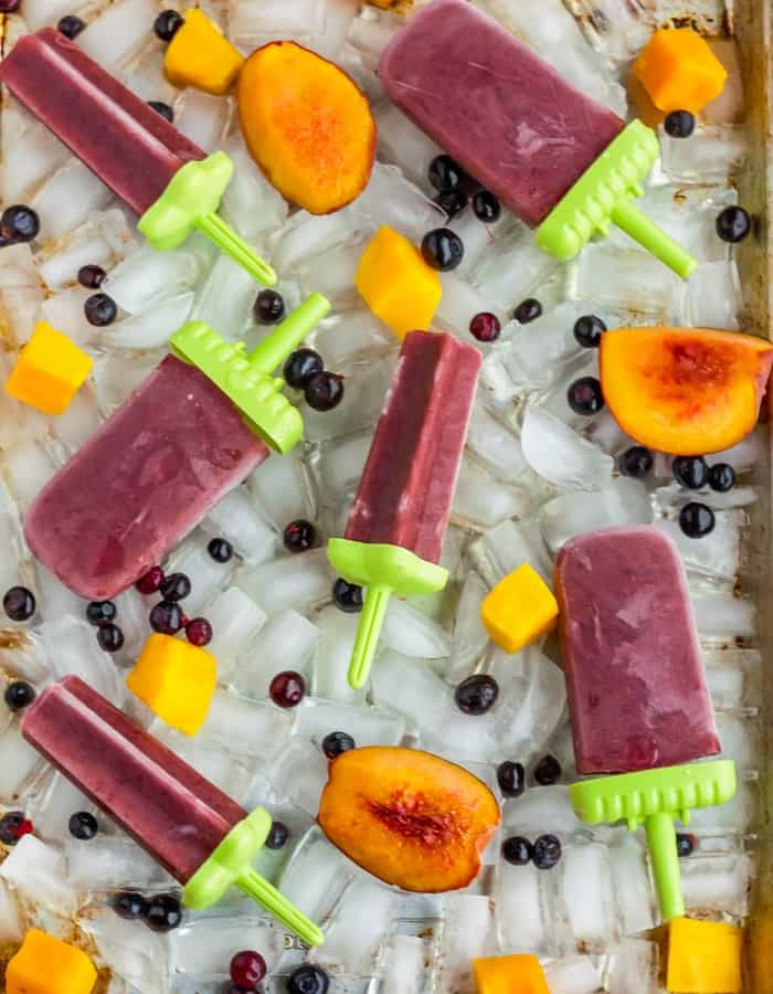 red healthy tea popsicles for sore throats and fruit on a tray of ice cubes