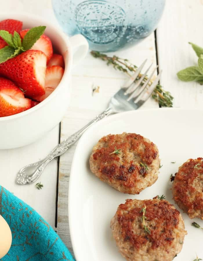 whole30 breakfast sausage on a plate with strawberries for whole30 breakfast ideas