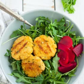 a bowl of arugula with three cauliflower patties and pickled vegetables