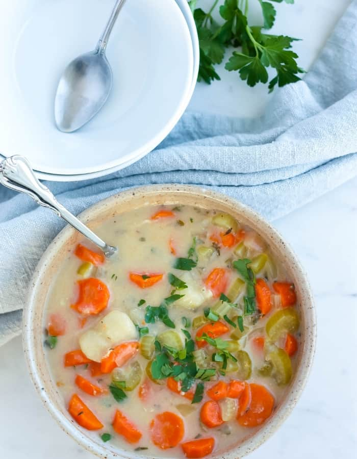 an overhead photo of a bowl of dairy-free chicken and gnocchi soup